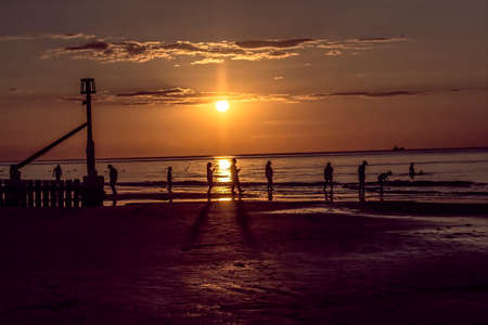 Pretty golden sunset with a sea groyne and people silhouettes. photo
