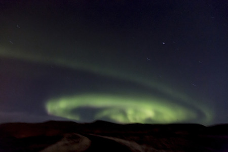 swirling: The northern lights (Aurora Borealis) swirling in the sky.