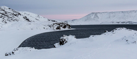 Panoramic photo of the Lake of Kleifarvatn, Reykjanes Peninsula, Iceland. The landscape is covered in snow and the sun is just coming up.