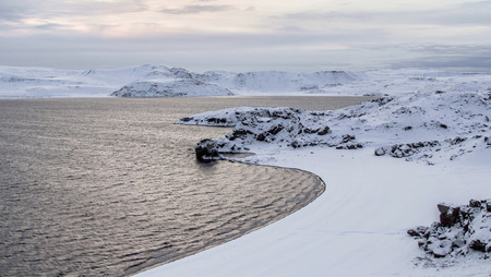 Close up photo of the water and snow by Lake of Kleifarvatn, Reykjanes Peninsula, Iceland. The landscape is cropped to show the shape and details in the water and snow, the sun is just rising and giving off a blue and yellow light Stock Photo