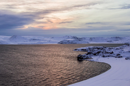 Photo of the sunrise at Lake of Kleifarvatn, Reykjanes Peninsula, Iceland. The landscape is covered in snow and the sun is just coming up. Photo taken in Iceland in December 2014