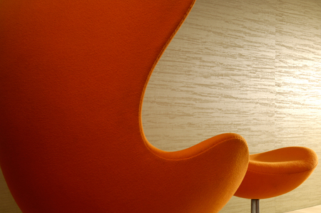 footstool: High Back Chair with Footstool in office hallway against wallpapered wall Stock Photo