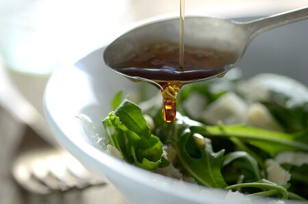 good cholesterol: Putting oil on the salad with fork in the background