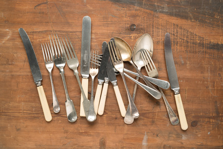 Variety of vintage cutlery layed out on wooden table.