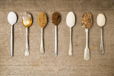 Seven teaspoons in a line with different types of sugar Stock Photo