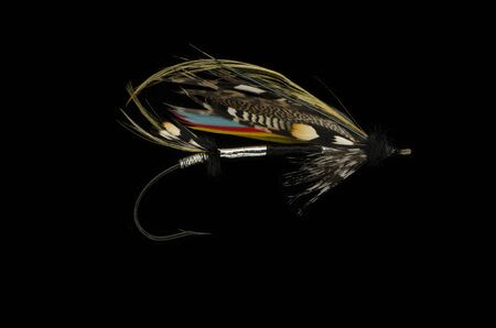 mar: Mar Lodge salmon fly shot against a black background Stock Photo