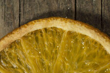 dried orange: Dried orange slice on a wooden background close up
