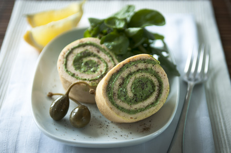 roulade: Salmon roulade on a white plate with capers and salad leaves