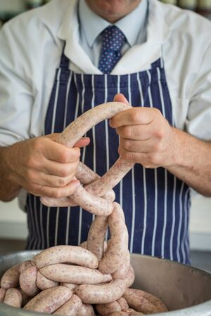 linking: Friendly butcher linking and preparing sausages Stock Photo