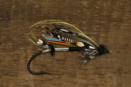durham: Traditionally dressed Durham Ranger salmon fly shot against a wooden background