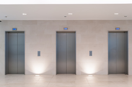 elevator: Three lift doors in office building Stock Photo