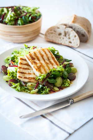haloumi: Haloumi and grape salad with mixed green leaves on a white plate