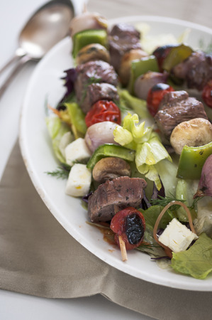 barbequing: Steak kebab on a skewer with tomatoes, mushrooms and peppers on top of a bed of salad
