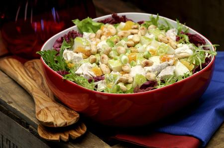 ensalada de verduras: ensalada de pollo de la coronación en un recipiente de color rojo con los servidores de ensalada en el lado Foto de archivo