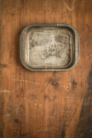 PrEP: Vintage rustic baking tray bowl with cutlery on wooden background.