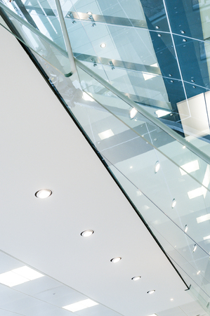 Looking upwards towards glass partitioning and ceiling lights in modern office 免版税图像