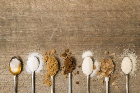 Seven teaspoons of assorted sugar spilling onto a wooden background 免版税图像 - 46034041