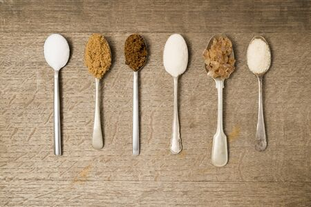 sugar spoon: Six teaspoons of assorted sugar on a wooden background