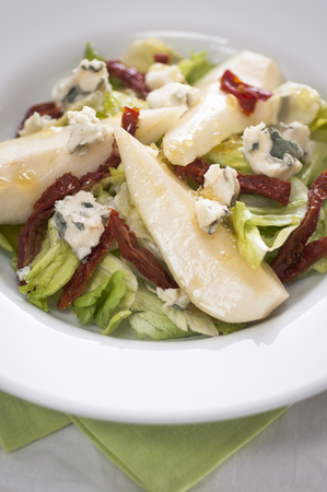 stilton: Pear, Stilton and Walnut Salad in a bowl with green lettuce and sundried tomatoes Stock Photo