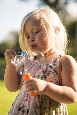 Child blowing bubbles with blurred background