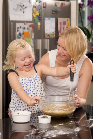 whisking: A mother and daughter having fun whisking cake mixture in a domestic kitchen