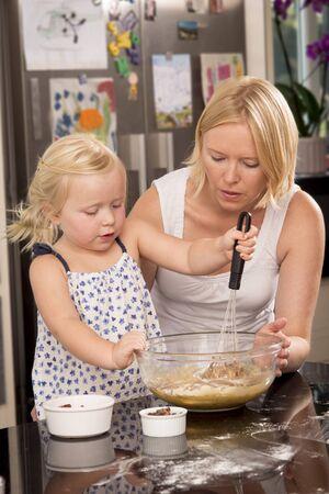 whisking: Child with mother whisking cake mixture Stock Photo