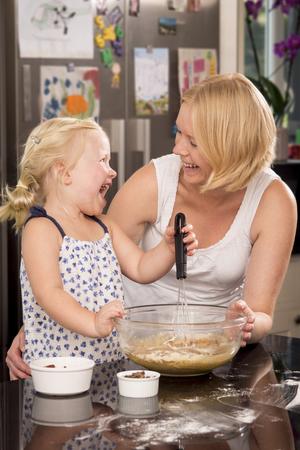 whisking: A mother and daughter having fun whisking cake mixture