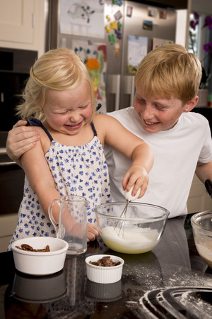 whisking: A brother and sister having fun whisking a cake mixture Stock Photo