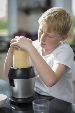 An eleven year old boy making a banana smoothie in a blender