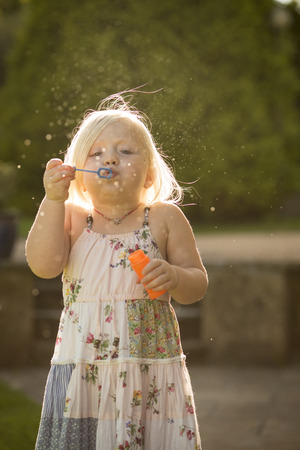 blowing bubbles: Child blowing bubbles with blurred background