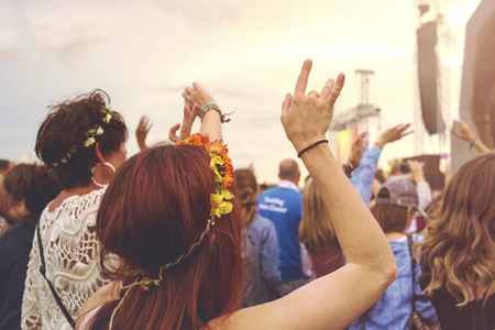 Crowd at an outdoor music festival with outstretched arms
