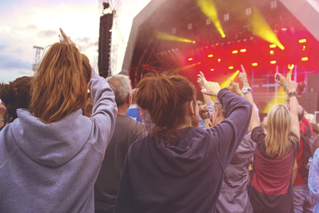 Crowd at outdoor music festival with outstretched arms looking towards stage Stock Photo