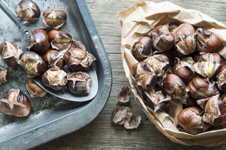 baking tray: Paper bag and baking tray with freshly roasted chestnuts