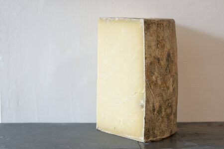 A wedge of montgomerys cheddar on slate and white wall behind