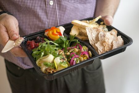 bento box: A bento box filled with salad, flatbread, pickled vegetables and a selection of british cheeses