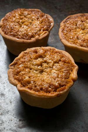 treacle: Three individual treacle tarts on a baking tray Stock Photo