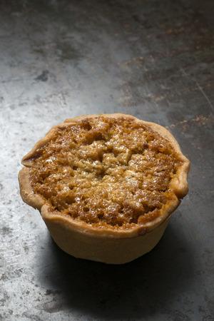 treacle: A single treacle tart on a worn baking tray Stock Photo