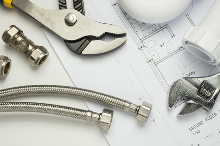 A selection of plumbing tools and fittings on domestic house plans 免版税图像 - 54755213