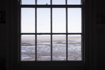 sash: The view through a sash window with a beach beyond