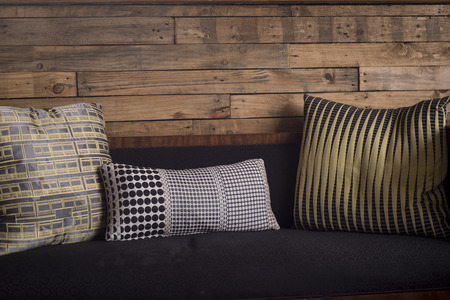 soft furnishing: Cushions on a sofa against a wooden plank wall