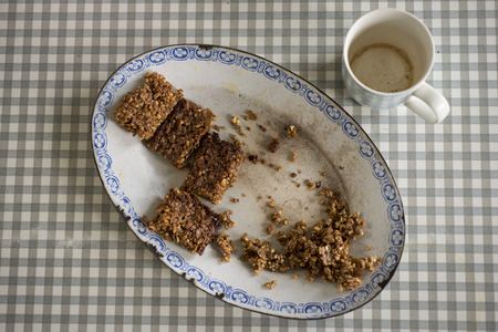 flapjacks: An oval vintage plate with a few remaining flapjacks and an empty cup to one side