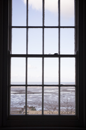 sash: Looking through a sash window with a beach beyond Stock Photo