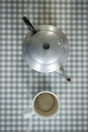 formica: Overhead shot of an aluminium teapot and empty mug on a vintage gingham formica table