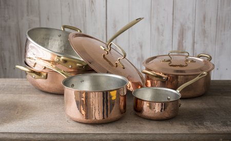 A set of copper cookware that include a small and medium-sized saucepan at front, a large saucepan, pot, and cover stacked on top of the other, and a covered small pot bringing up the rear, all placed on a wooden countertop.