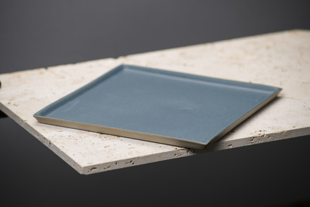 stoneware: An empty blue square dining plate or tray on a stone countertop.