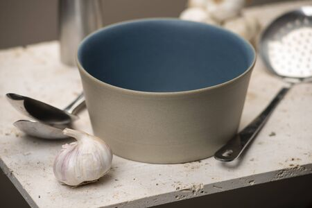 slotted: An empty beige flat bottom soup bowl with blue interior, alongside a pair of spoons, a slotted spoon, and garlic all on a stone countertop.