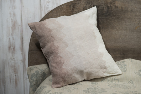 headboard: A square throw pillow with gradient brown zigzag design, leaning on a wooden headboard.