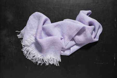 fringes: A lavender hand towel with white fringes placed at center of a dark surface. Stock Photo