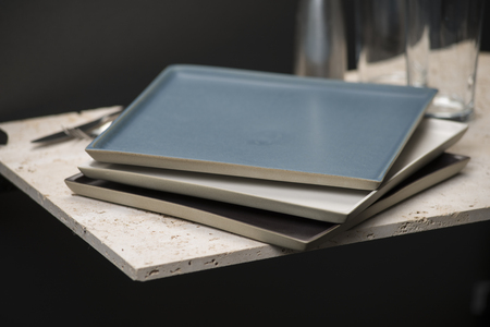 fork glasses: A stack of three square dining plates or trays of varying color interior alongside knife, fork, salt shaker, and a pair of drinking glasses on a stone countertop. Stock Photo
