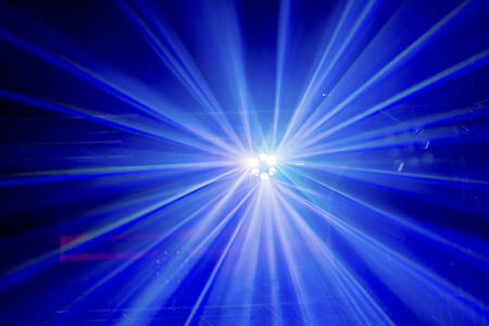Multicoloured light beams from a high up disco stage light